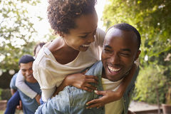 Two adult black couples piggybacking looking at each other royalty free stock images