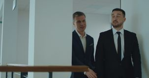 Businessmen walking in office. Two adult businessmen in suits walking and talking in office hallway. Slow motion. Shot on Red cinema camera stock footage