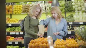 Two adult Caucasian housewives picking tangerines in grocery. Serious senior women putting fruits into paper pack and
