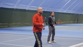 Two adult men play tennis in a couple. Two adult caucasian men are playing tennis at the indoors court. Friends play in a pair and professionally hits the balls stock video