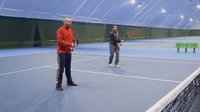 Two caucasian men play tennis at indoors court. Two adult caucasian men are playing tennis at the indoors court. Friends play in a pair and professionally hits stock footage