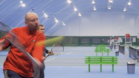 Two friends play tennis in couple. Two adult caucasian men are playing tennis at the indoors court. Friends play in a pair and professionally hits the balls to stock video footage