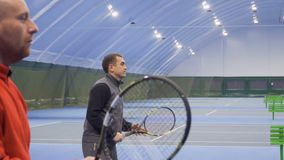 Two men play tennis in a couple at the court. Two adult caucasian men are playing tennis at the indoors court. Friends play in a pair and professionally hits the stock video