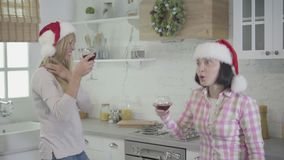 Two adult Caucasian women in red Christmas hats dancing and singing as drinking wine at modern kitchen. Cheerful friends stock footage