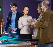 Two adult couples of different generations are drinking wine in Royalty Free Stock Images