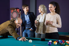 Two adult couples of different generations talk in the billiard royalty free stock photos