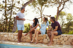 Two adult couples socialising outdoors by a swimming pool Stock Image