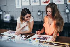 Two adult female students working on their paintings studying at art school royalty free stock photography