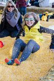 Two adult females bury each other in a corn pit at a corn maze royalty free stock image