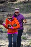 Two adult females happily walk with an armful of large Jeffrey pine cones found on the forest floor royalty free stock images