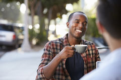 Two adult male friends sit talking over coffee outside cafe Royalty Free Stock Images