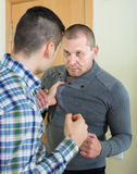 Two adult males fighting indoor Royalty Free Stock Images