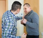 Two adult males fighting indoor Royalty Free Stock Photography