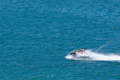 Males Riding Jet-ski at Sea stock photo
