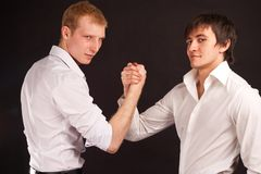 Two adult man in business hand shake. On black backdrop Royalty Free Stock Photos