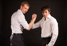 Two adult man in business hand shake on black back Royalty Free Stock Image