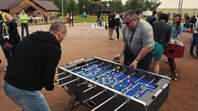 Two adult men absorbedly play american table soccer. Sand. Summer festival stock video
