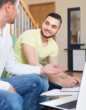 Two adult men with laptop indoors Royalty Free Stock Photos
