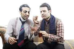 Teabaging Wannabe Seniors. Two adult men (mid 30's and mid 20's) wearing old-man clothes and makeup, sitting on a used up vintage sofa. They seems to be sharing Royalty Free Stock Photos