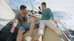 Two adult men sail on the sea on a yacht, a sea vehicle staggers under small waves, friends talk and actively spend the. Two men sit on the deck of the boat stock video footage