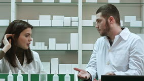Two adult pharmacists having conflict, discussing problems at pharmacy. Close up. Professional shot in 4K resolution. 081. You can use it e.g. in your stock video