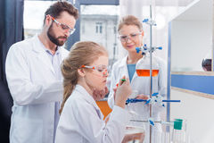 Two adult scientists and little girl student making experiment Stock Photography