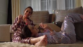 Two adult sisters twins having fun blowing bubbles wearing pretty pajams on the background of cozy living room