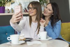 Two friends sit and photograph themselves with a smartphone. Two adult smiling girls with glasses take pictures of themselves with a smartphone Royalty Free Stock Photos
