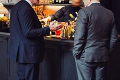 Two adult successful businessmen discuss and talk about business deal in the bar while they drinking at the evening. Stock Photo