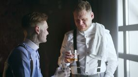 Two adult tattoed friends drinks whiskey and have a talk, 30`s mafia style, gangsters bar, 4k UHD 60p Prores HQ 422. Two adult tattoed friends drinks whiskey and stock video footage