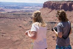 Two adult woman mother and daughter enjoy the scenic view of the Canyonlands National Park in Utah stock photos