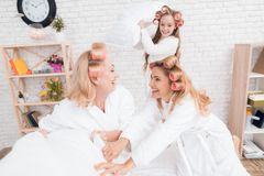 Two adult women and a girl play a fight with pillows on the bed. They have curlers on their heads. They are in a good mood royalty free stock photo