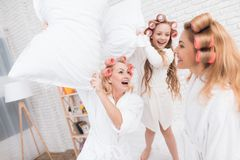 Two adult women and a girl play a fight with pillows on the bed. They have curlers on their heads. They are in a good mood stock image