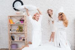 Two adult women and a girl play a fight with pillows on the bed. They have curlers on their heads. They are in a good mood royalty free stock photos