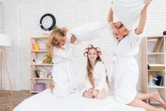 Two adult women and a girl play a fight with pillows on the bed. They have curlers on their heads. They are in a good mood royalty free stock image