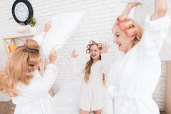 Two adult women and a girl play a fight with pillows on the bed. They have curlers on their heads. They are in a good mood stock photos