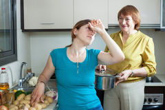 Two adult women   in kitchen at home Royalty Free Stock Photo