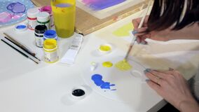 Two adult women paint with colored acrylic paints in an art school close up. 4k