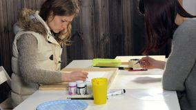 Two adult women paint with colored acrylic paints in an art school. 4k