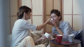 Two adult women sitting at the small table on comfortable pillow chairs drinking coffee and talking about cosmetics. Younger lady shows her friend a new cream stock video