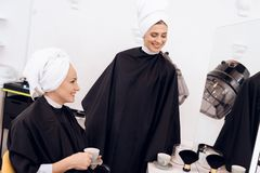 Two adult women with towels on their heads drinking coffee at hairdresser`s salon. stock photography