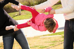 Two adults fighting for a child. A picture of two adults fighting for an innocent child in the park Royalty Free Stock Photo