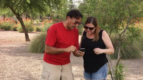 Two Adults Play Augmented Reality Game on Smartphone. Two adults play the popular augmented reality game Pokemon Go outside in a public park stock footage