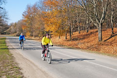 Two adults riding bikes Stock Image