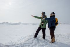 Two adventurous women pointing into distance. Standing on a frozen lake in winter Royalty Free Stock Images