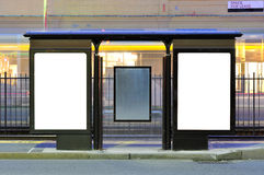 Two Advertisment Billboards at Train Stop. Two advertisement billboards side by side at train stop, blur lights of train passing by, store fronts in the Royalty Free Stock Photography