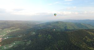Two aerostat flying at different heights above the forest. Rolling hills, dense forest with high green trees, you can see river and village, blue sky, last stock video footage