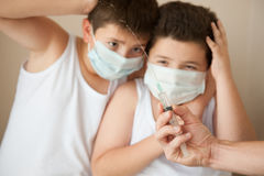 Two afraid boys in medical mask looking at hand with syringe Royalty Free Stock Photos