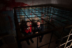 Two afraid Halloween victims imprisoned in a metal cage Stock Image