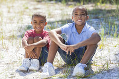 Two African American Boys Outside. Two young African American boy children sitting together in the summer sunshine Stock Photos